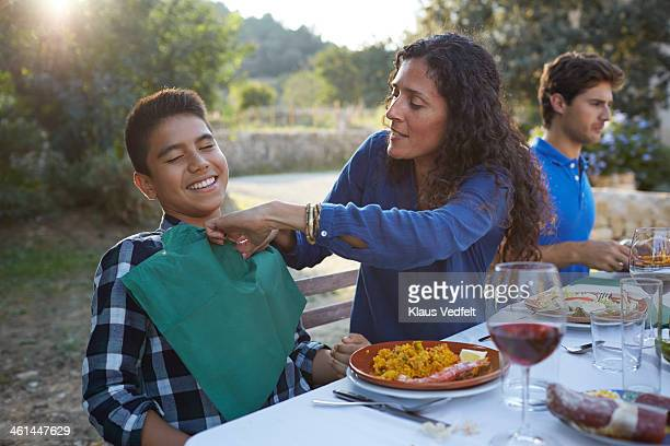 Mother helping son, stuffing napkin down his shirt