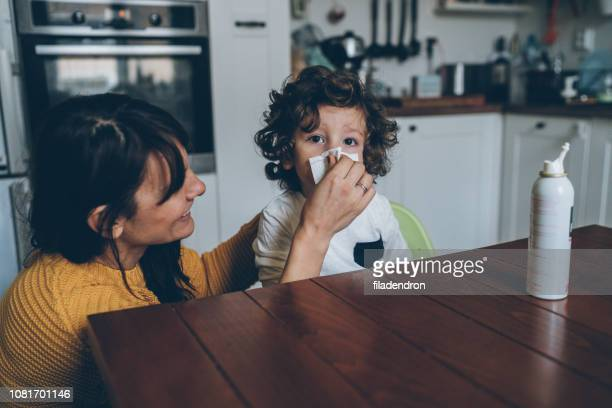 mother helping son to blow his nose - blowing nose stock pictures, royalty-free photos & images