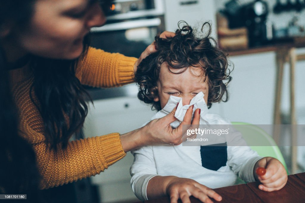 Mother helping son to blow his nose : Stock Photo