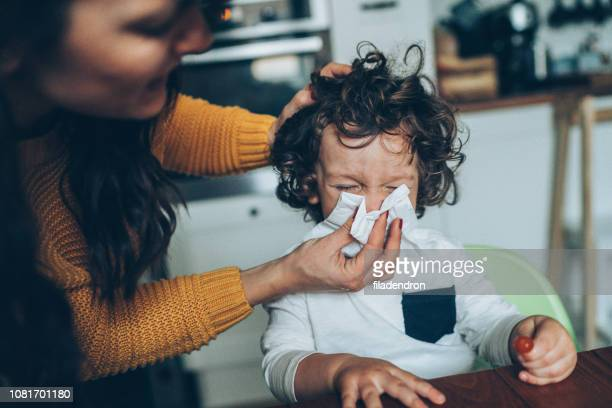 mother helping son to blow his nose - cold virus stock pictures, royalty-free photos & images