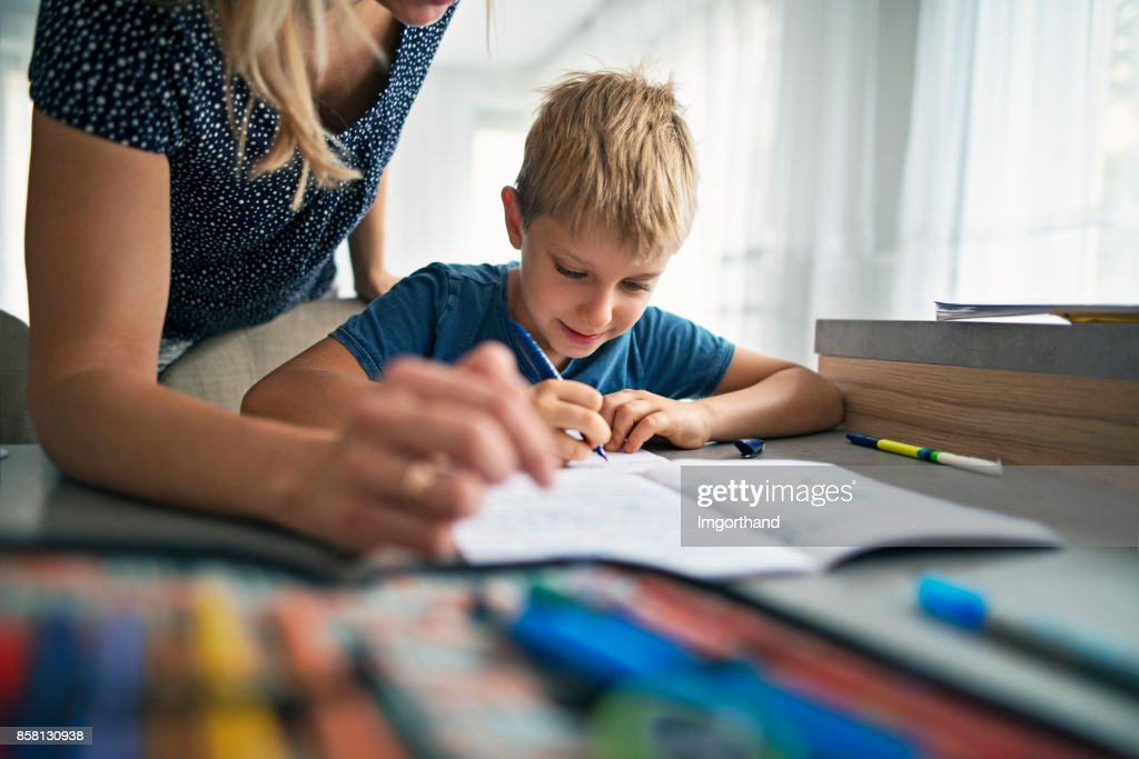 Mother helping son to do his homework : Stock Photo