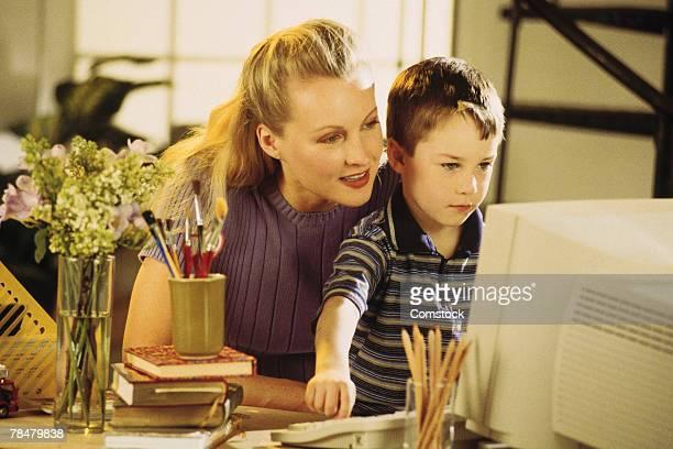 mother helping son use home computer - 1990 1999 fotografías e imágenes de stock