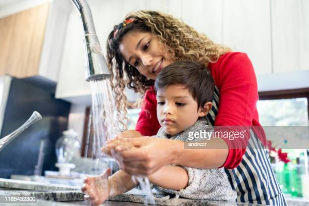mother helping son wash his hand after making cookies - hand wash stock pictures, royalty-free photos & images