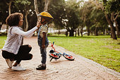 Mother helping son wearing helmet for cycling