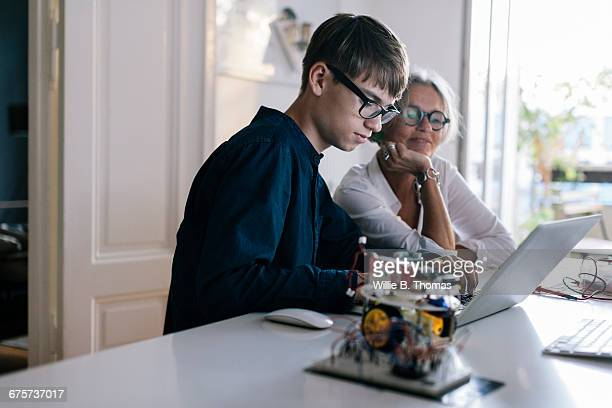 Mother helping son with computer coding