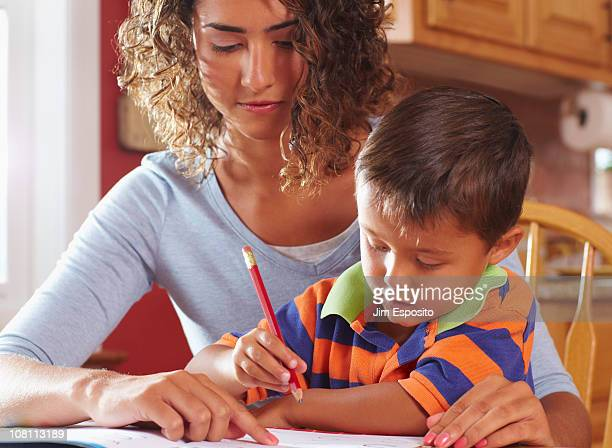 mother helping son with homework - mom sits on sons lap stock pictures, royalty-free photos & images