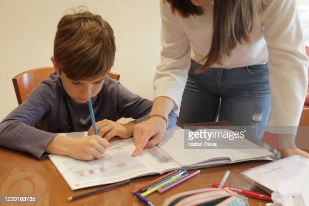 mother helping son with homework - ホームスクーリング ストックフォトと画像