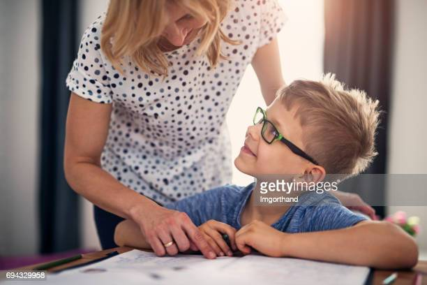 mother helping son with homework - homeschool stock photos and pictures