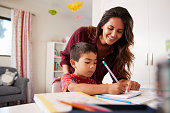 Mother Helping Son With Homework Sitting At Desk In Bedroom