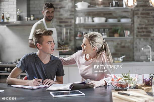 Mother helping son with homework while father is cooking