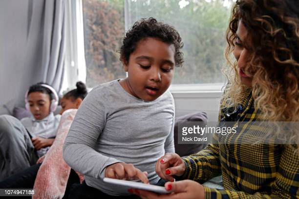 Mother helping son with tablet with siblings in the background
