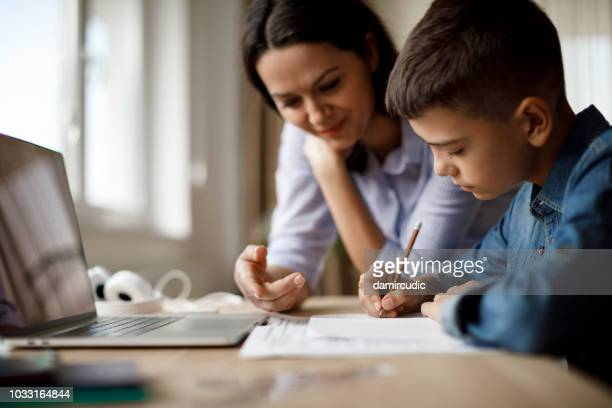 mother helping teenager with homework - teaching stock pictures, royalty-free photos & images