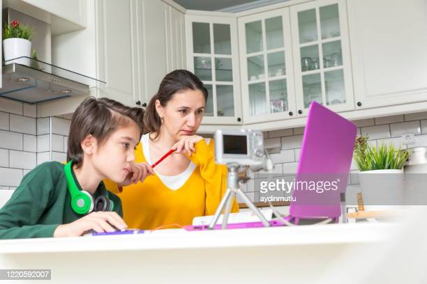 mother helping teenager with homework - distante foto e immagini stock