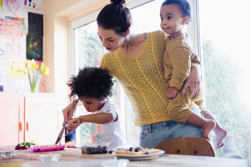 Mother helping toddler daughter cutting breakfast waffles - gettyimageskorea