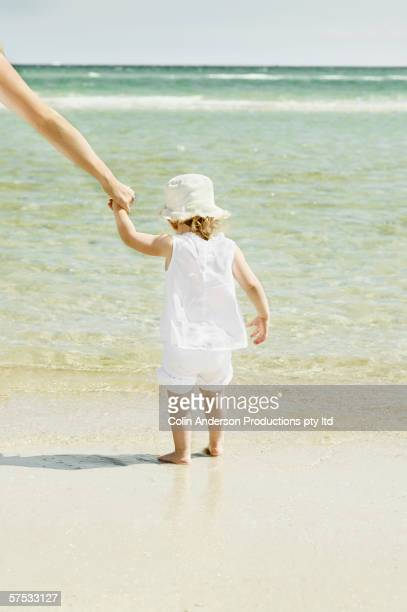 Mother helping toddler daughter walk on the beach