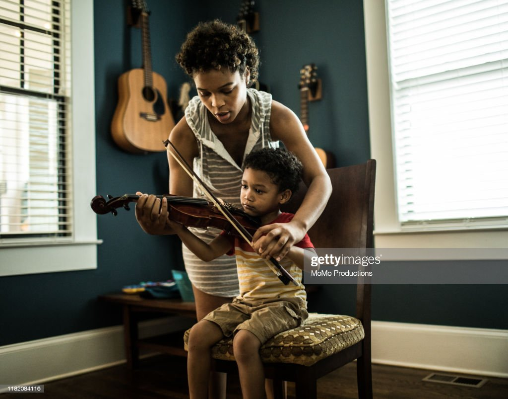 Mother helping young boy (3 yrs) practice violin : Stock Photo