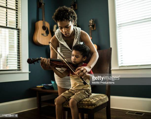 mother helping young boy (3 yrs) practice violin - musical instrument stock pictures, royalty-free photos & images
