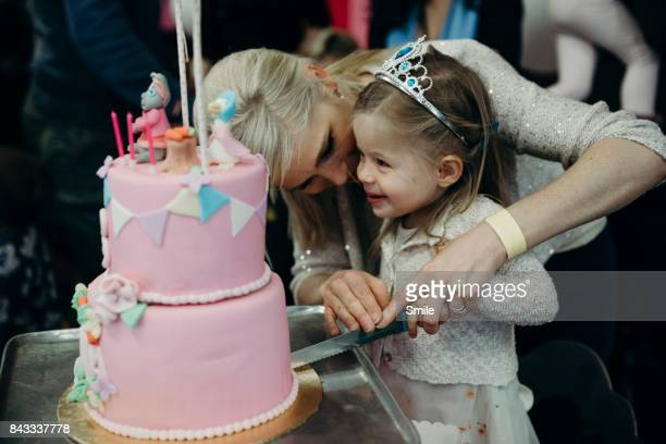 mother helping young girl cut birthday cake - cake stock pictures, royalty-free photos & images