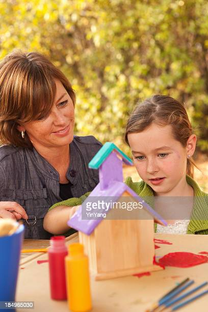 Mother Helping Young Girl with Birdhouse Painting Project Outdoors Vt