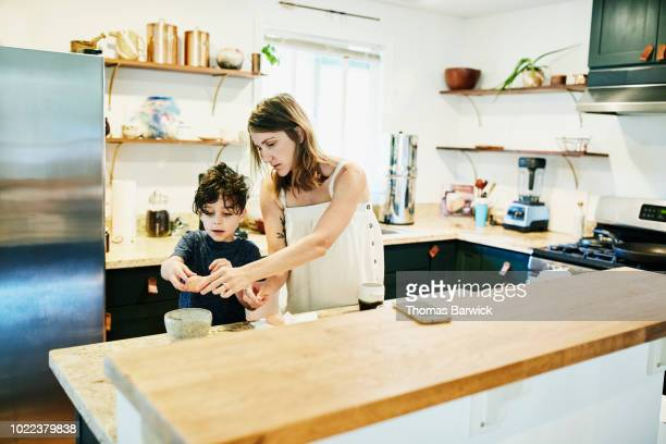 Mother helping young son crack egg into bowl while making breakfast in kitchen
