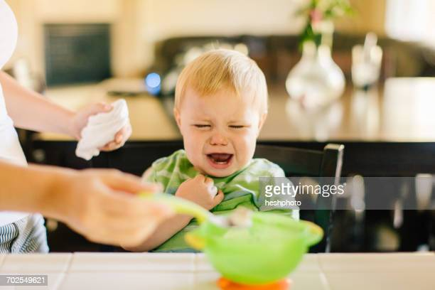 Mother helping young son eat breakfast, son crying, mid section