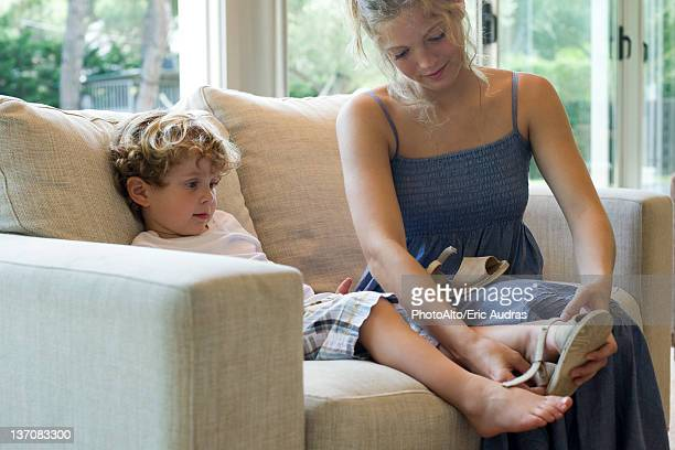 Mother helping young son put on shoes