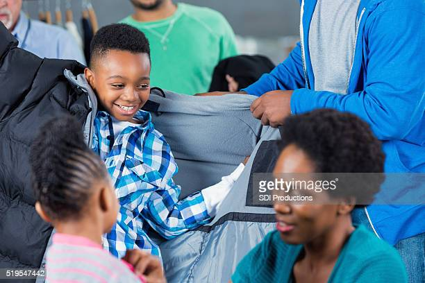 Mother helps children put on coats at clothing drive