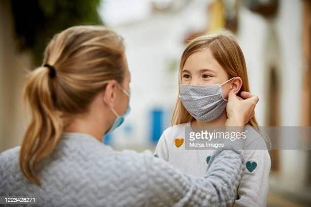 une mère aide sa fille à mettre un masque fait maison pour covid-19 - filiation photos et images de collection