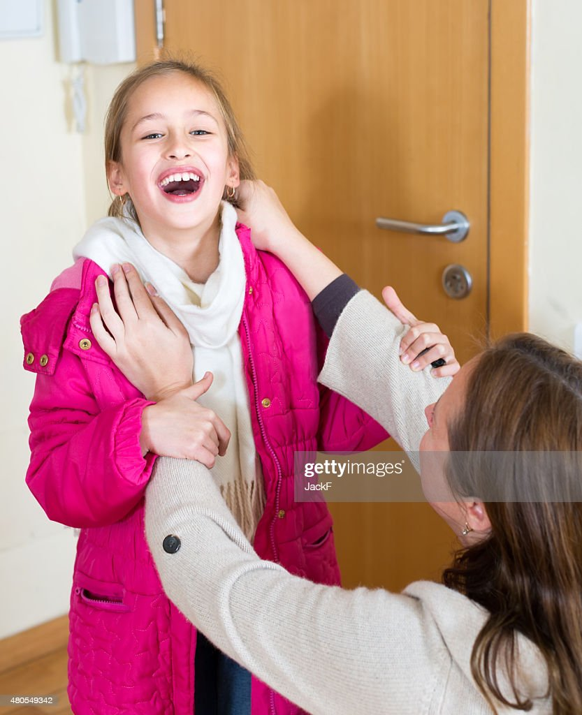 Mãe ajuda a menina de Vestido : Foto de stock