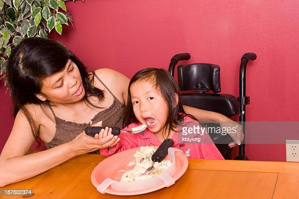 mother helps daughter use adaptive silverware - filipino family eating stock pictures, royalty-free photos & images