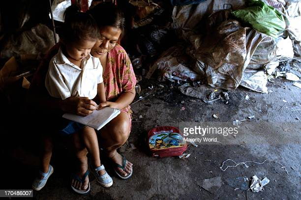 A mother helps her child during the class at emergency school under the highway flyover This free school was founded by the twins Rosy and Ryan in...