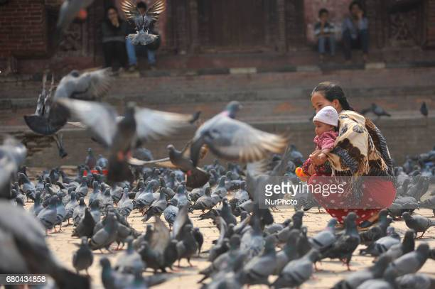 A mother helps her child to plays with pigeons at Basantapur Durbar Square Kathmandu Nepal on Monday May 08 2017 Basantapur Durbar Square is one of...