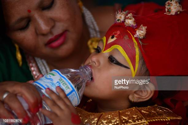 A mother helps her daughter to drink water during the celebration of Kumari puja at Basantapur Durbar Square Katmandu Nepal on Tuesday September 11...