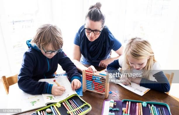 A mother helps her nineyearold son and sixyearold daughter to do school homework on March 15 2020 in Dinslaken Germany Schools day care centers and...