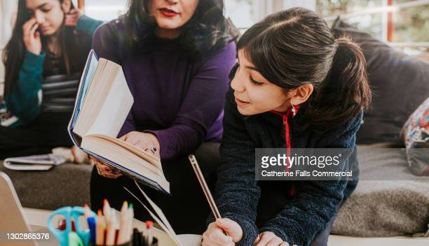 a mother helps her younger daughter with her homework while older teenager reads in the background - preschool child stock pictures, royalty-free photos & images