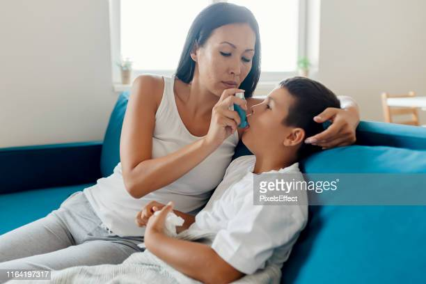 mother helps son to use an inhaler against asthma - cystic fibrosis stock photos and pictures
