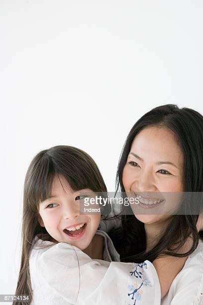 Mother hodling daughter, smiling