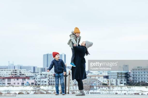 mother holding a child - yusuke nishizawa stock-fotos und bilder