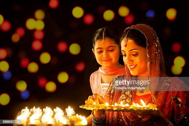 mother holding a tray of diyas while her daughter looks on - diwali celebration stock photos and pictures