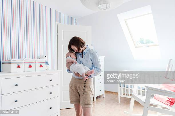 Mother holding and cuddling little baby boy tenderly, baby's room