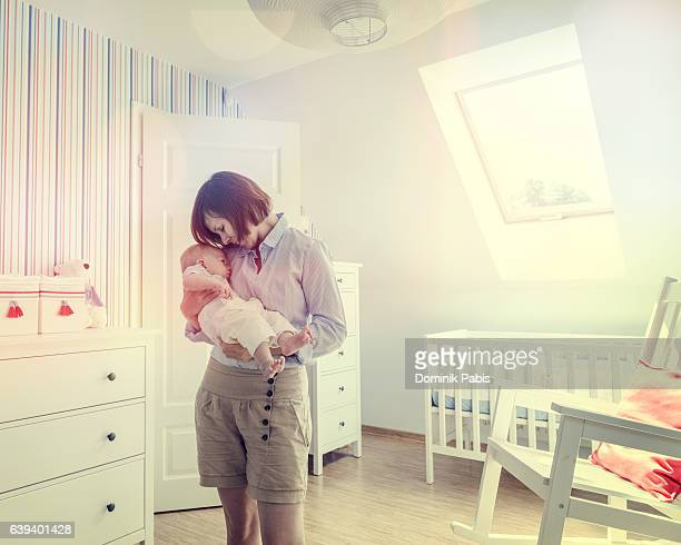 Mother holding and hugging little baby boy tenderly, baby's room