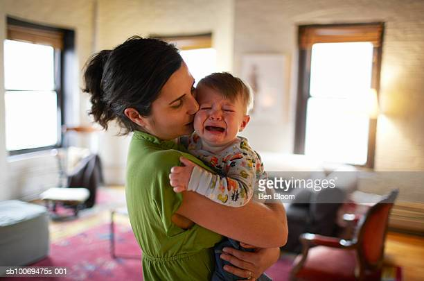 Mother holding and kissing crying baby boy (12-17 months) (focus on foreground)
