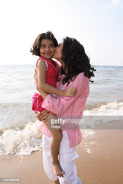 mother holding and kissing her daughter on the beach - indian girl kissing stock photos and pictures