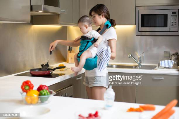 Mother holding baby and cooking in the kitchen