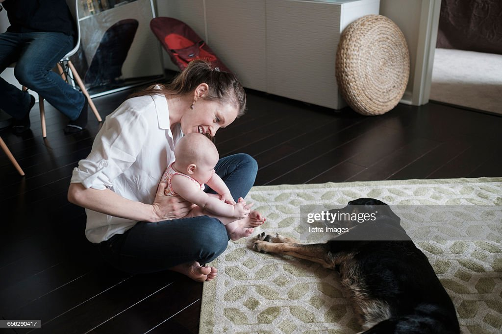 Mother holding baby (2-5 months) and playing with dog : Stock Photo