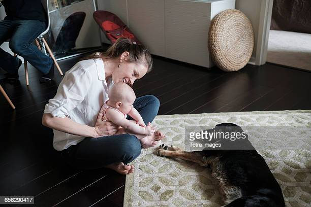Mother holding baby (2-5 months) and playing with dog