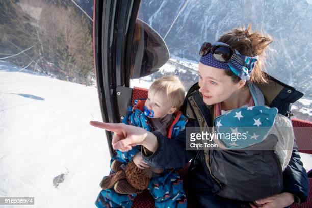 mother holding baby and sitting next to toddler in gondola, pointing at something - gondel stock-fotos und bilder