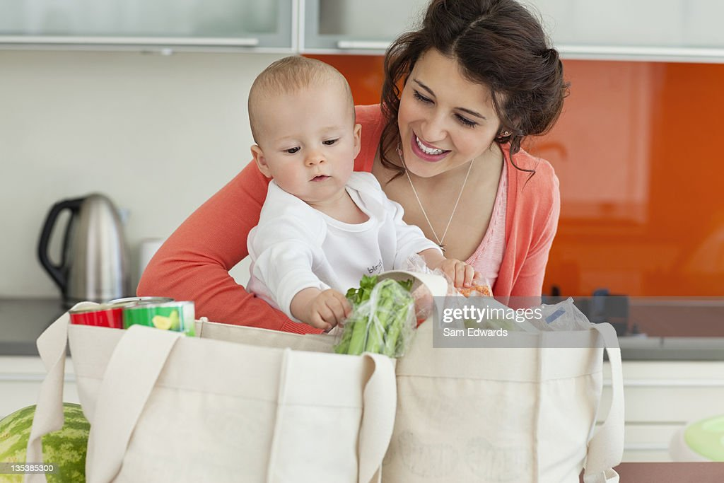 Mother holding baby and unloading groceries : Stock Photo