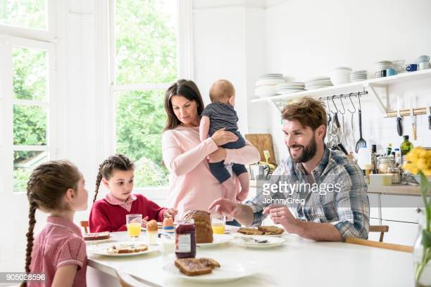 Mother holding baby as father sits and eats breakfast with daughters around kitchen table