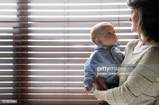 mother holding baby boy and looking out blinds - baby depression stock pictures, royalty-free photos & images